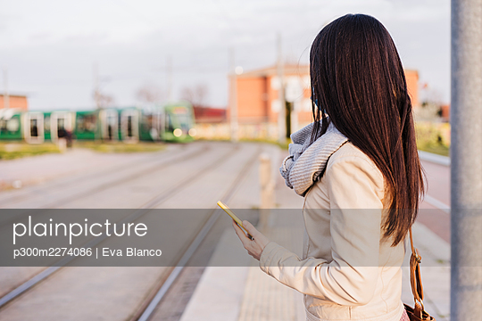 Woman with long hair holding smart phone while waiting for train at railroad platform - p300m2274086 by Eva Blanco