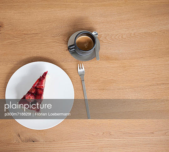 Strawberry cake with coffee cup on table - p300m718829f by Florian Löbermann