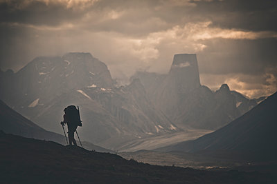 Silhouette of backpacker hiking through rugged mountain landscape - p1166m2189996 by Cavan Images