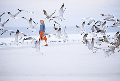 Woman walking next to the ocean surrounded by flying seagulls - p1577m2150324 by zhenikeyev