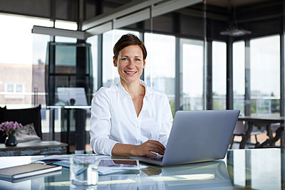 Portrait of smiling businesswoman sitting at glass table in office with laptop - p300m2012983 von Rainer Berg