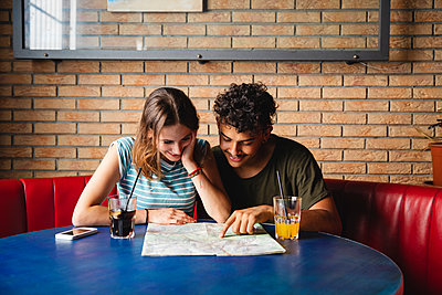 Smiling young couple sitting at table in a cafe with map - p300m2042905 von Michela Ravasio