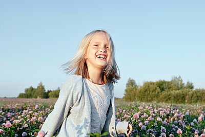 Portrait of a smiling girl standing on a clover field - p300m2143853 by Ekaterina Yakunina