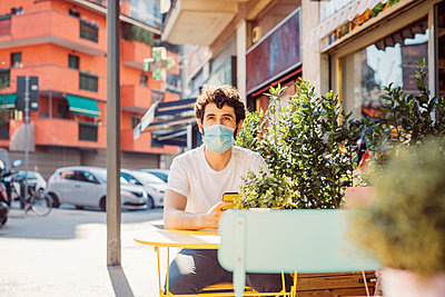 Thoughtful young man wearing mask sitting at sidewalk cafe in city - p300m2202883 by Eugenio Marongiu