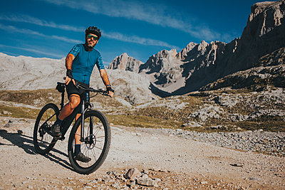 Mountain cyclist with bicycle exploring Picos de Europa National Park, Cantabria, Spain - p300m2240202 by David Molina Grande