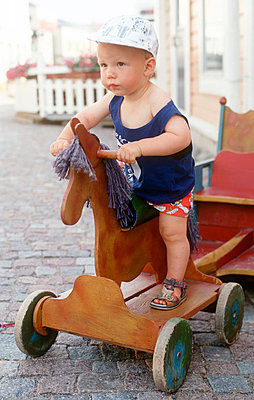 Young boy riding on toy horse - p3226880 by Kimmo von Lüders