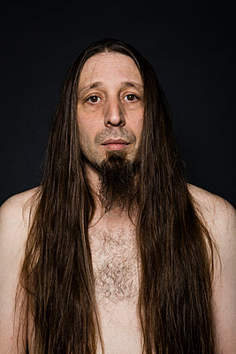 Portrait of a long-haired shirtless man with a goatee - p590m1508112 by Philippe Dureuil