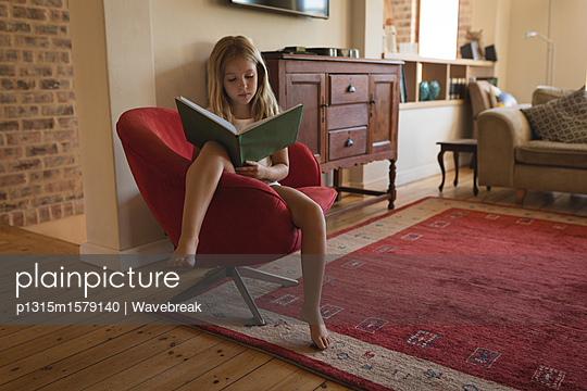 Girl studying in living room - p1315m1579140 by Wavebreak