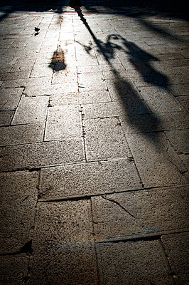 Shadow of street lamp on paving stones - p1047m1215472 by Sally Mundy