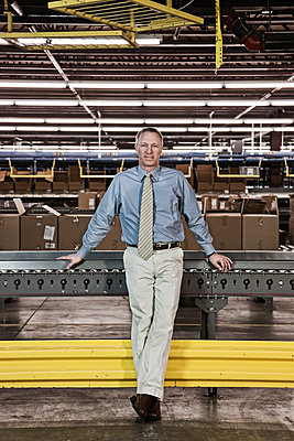Portrait of a male Caucasian executive in a dress shirt and tie  next to a motorized conveyor system in a large distribution warehouse. - p1100m1575465 by Mint Images