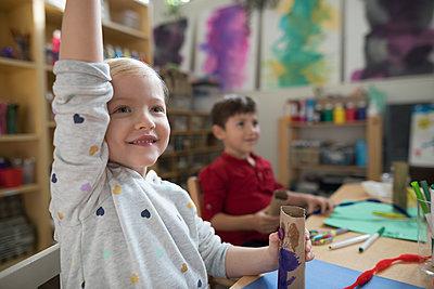 Eager preschool girl raising hand in art class - p1192m1560106 by Hero Images