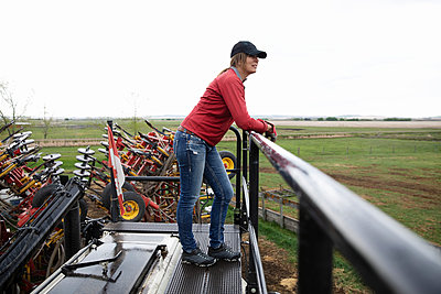 Female farmer standing on top of tractor machinery on farm - p1192m2109746 by Hero Images