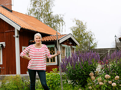 Smiling woman standing in front of house - p312m800526f by Plattform