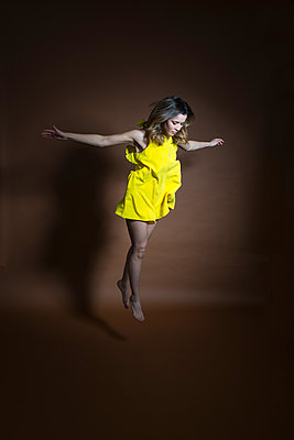 Hovering young woman in yellow dress - p427m2063086 by Ralf Mohr
