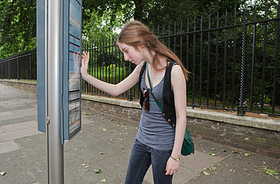Young woman looking at bus time table - p42910947f by Clarissa Leahy