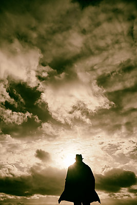 Rearview man in hat and coat with low sun and stormy clouds - p597m2230604 by Tim Robinson