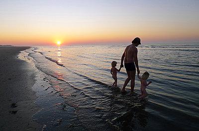 Familie am Strand bei Sonnenuntergang - p896m834755 von Amber Beckers