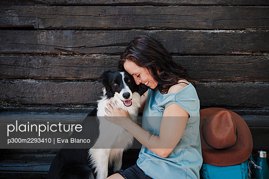 Smiling woman with eyes closed embracing dog while sitting in front of cottage - p300m2293410 by Eva Blanco