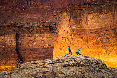 Two women doing yoga outdoors in the desert at sunrise. - p1166m2113596 by Cavan Images
