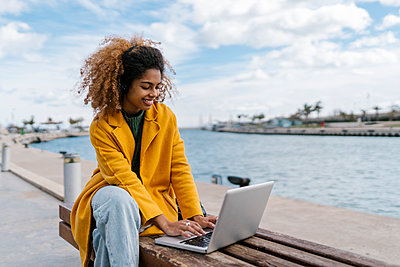 Smiling Afro woman using laptop while sitting on bench at river - p300m2265574 by Ezequiel Giménez