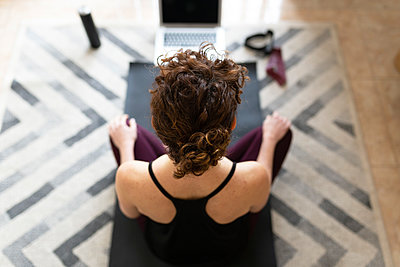 Woman on exercise mat practicing yoga at home - p300m2282267 by Sus Pons
