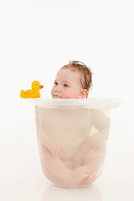 A baby girl sitting in a bucket of water - p301m714135f by Julia Christe