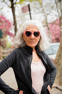 Older woman wearing heart-shape sunglasses - p555m1491483 by JGI/Jamie Grill