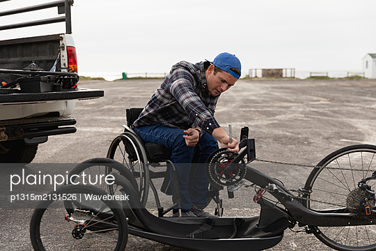 Disabled man in a wheelchair enjoying a day out - p1315m2131526 by Wavebreak
