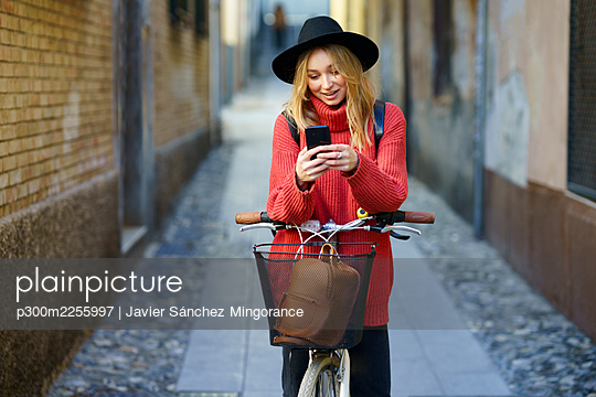 Blond woman using smart phone while standing with bicycle on footpath - p300m2255997 by Javier Sánchez Mingorance