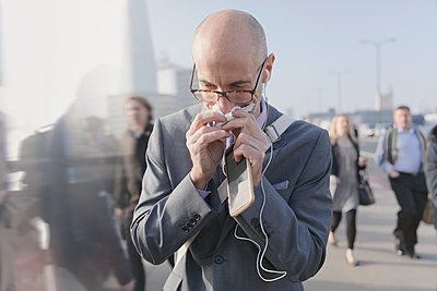 Businessman blowing nose with tissue, holding cell phone and headphones on urban pedestrian bridge - p1023m1485653 by Tom Merton