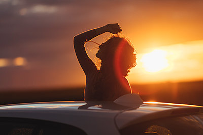 Woman outside the car at sunset, raised arm - p300m1581622 von Javier Pardina