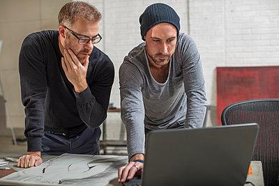 Artist using laptop with man in studio - p300m2013316 von zerocreatives
