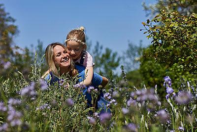 Happy mother carrying daughter piggyback in allotment garden - p300m2198607 by Maya Claussen