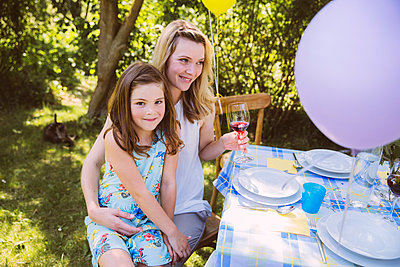 Daughter sitting on mother's lap at garden party table - p300m981474f by Mareen Fischinger
