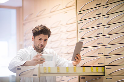 Young male pharmacist using digital tablet and reading medical drug packet in pharmacy - p429m1547912 by Sigrid Gombert