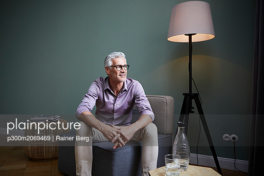 Mature man sitting on armchair at home - p300m2069469 by Rainer Berg