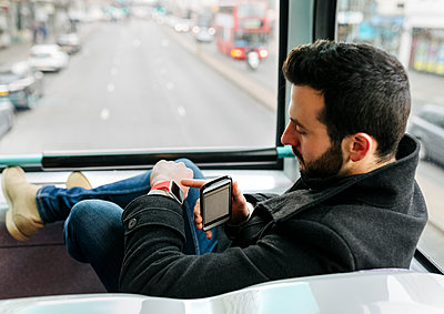 UK, London, young man in a double-decker bus using his smartwatch - p300m1130070f von Marco Govel