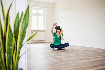 Woman in empty apartment wearing VR glasses - p300m1460012 by Uwe Umstätter