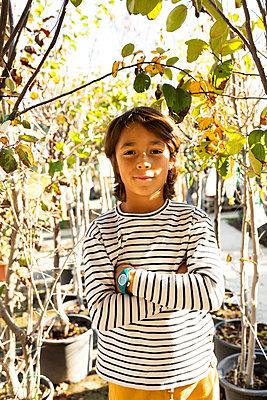 Portrait of boy at plant nursery - p300m2155865 by Valentina Barreto