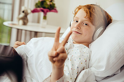 Sick boy lying in hospital making victory sign, wearing head phones - p300m2214191 by Mareen Fischinger