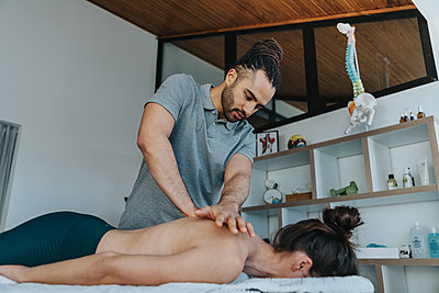 Physiotherapist giving massage to spine and upper back of female patient in medical practice - p300m2276735 by Mareen Fischinger