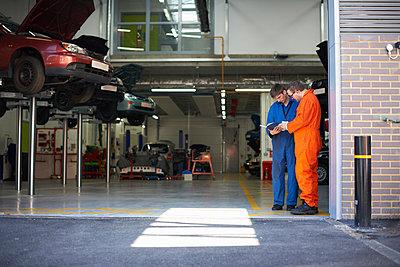 College mechanic students reading manual in repair garage - p429m1227044 by Peter Muller