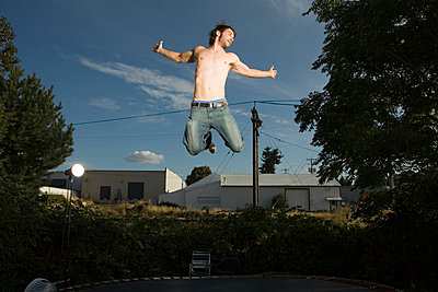 Young man jumping in mid-air, low angle view - p4341690 by Alin Dragulin