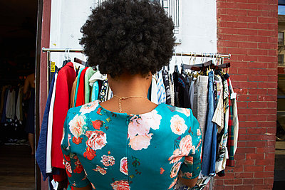 Rear view of young female fashion blogger with afro hair looking at vintage clothes rail, New York, USA - p924m1422626 by Karen E. Evans