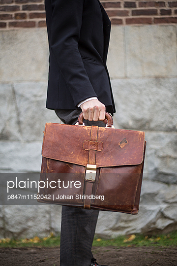 A man in a suit carrying a briefcase in leather   - p847m1152042 by Johan Strindberg