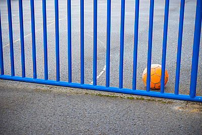 Orange football next to blue fence  - p1302m1588938 by Richard Nixon