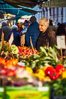 Mann begutachtet Gemüse an einem Gemüsestand in Venedig - p1312m2082188 von Axel Killian