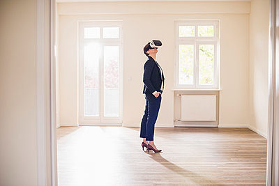 Woman in empty apartment wearing VR glasses - p300m1459930 by Uwe Umstätter