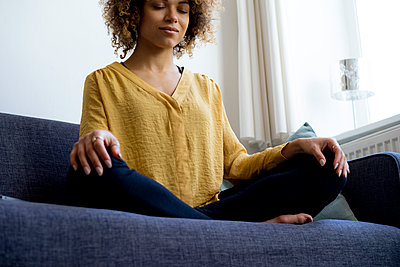 Young woman sitting on couch at home meditating - p300m1535933 by harry + lidy