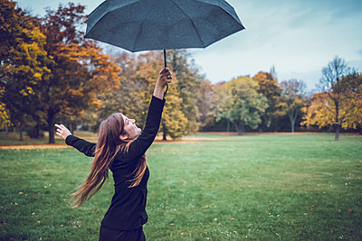 Happy young woman dancing with umbrella in autumnal park - p300m1563322 by Jonathan Schöps